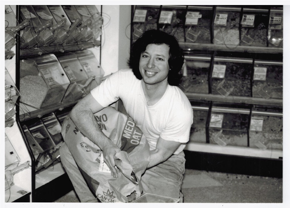 Black and white photo of a smiling young man filling a bulk bin