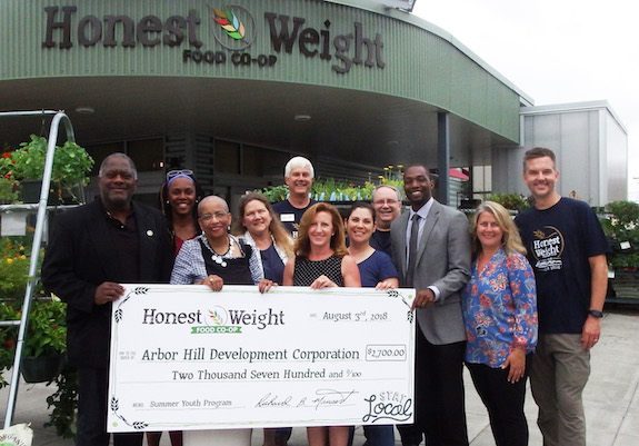 A group of people standing in front of Honest Weight holding a large check for $2,700 made out to Arbor Hill Development Corp from Honest Weight Food Co-op