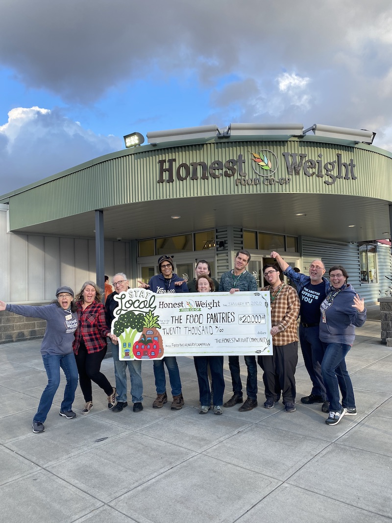 Happy Honest Weight staff standing in front of their store holding a large check for $20,000 made out to The Food Pantries